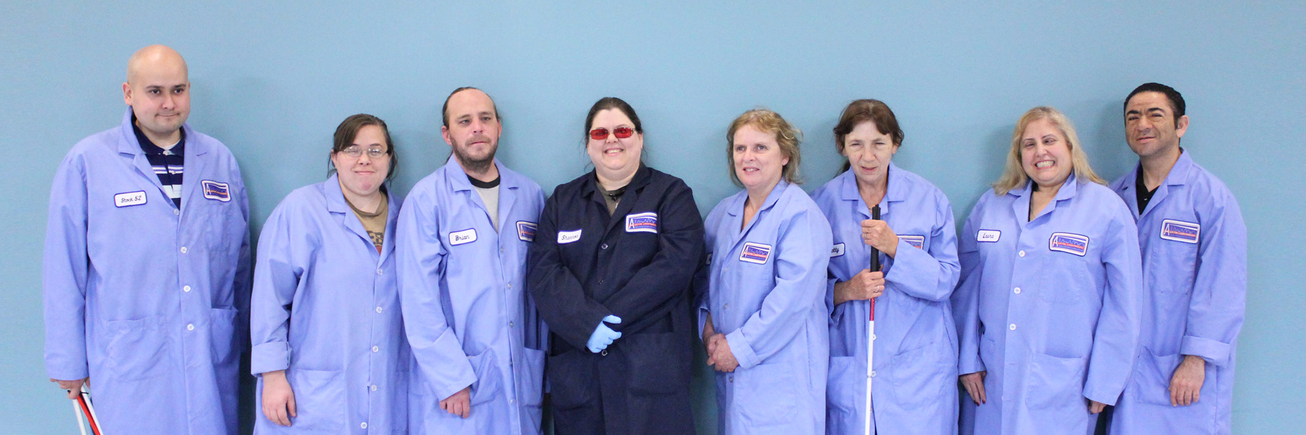 Austin Lighthouse Team dressed in manufacturing uniforms.